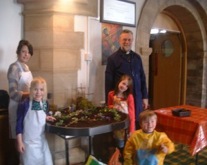 Photo: Chris Burch with some children and their completed Easter Garden