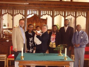 Photo: Chris, Pat, Jemima, Roz, Ellie, Basiki and Austin standing behind the Altar