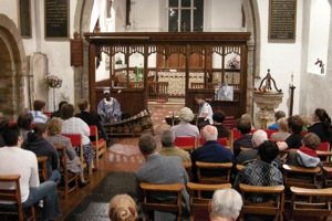Photo: Thomas and Bex perform, while the audience listen in church