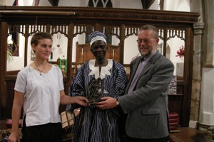 Photo: Bex and Thomas present a gift from Thomas to Chris Burch (our Vicar, and Bex's Dad)